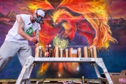 Brand Rockwell (aka Brandalizm), of Boston, spray-paints a mural during the 2nd annual Noshbow.