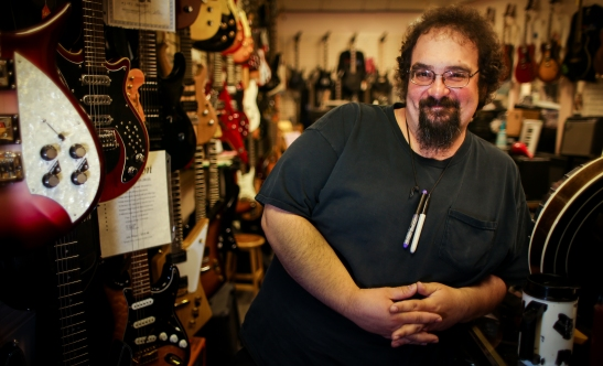 Mark Belanger, of Pigboat, stands among the instruments at Guitar Grave, his place of employment. Pigboat released its latest album this week and plays a release party Friday at Geno's Rock Club.