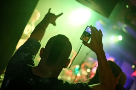 A mohawked man throws up the horns while videotaping a set by Murcielago during the band's CD release party earlier this month.